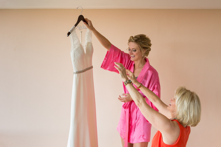 bride looking at the wedding dress with mom