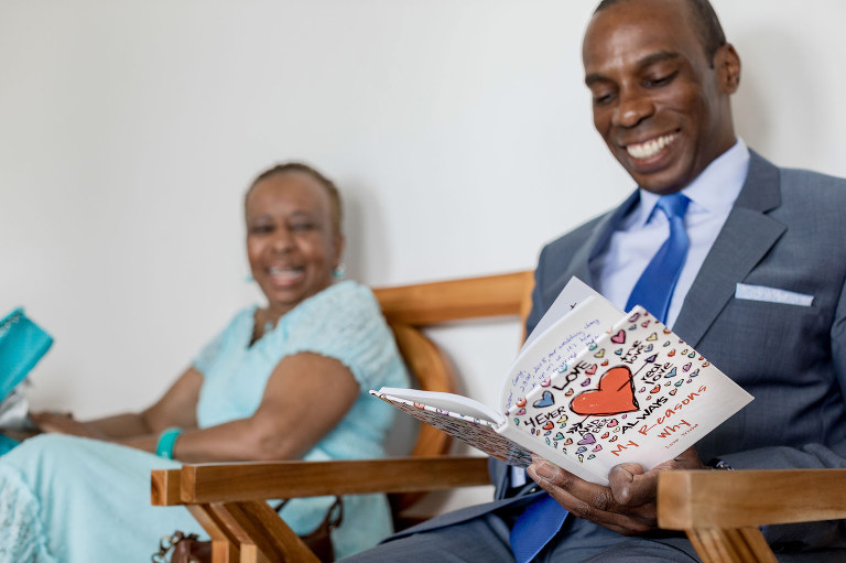 The groom smiling as he reads the book gifted to him by the bride
